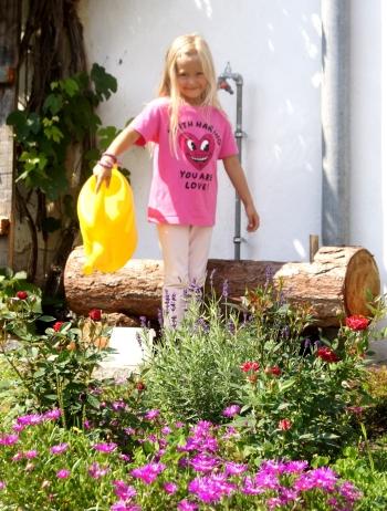 Junge Hofbewohnerin beim Blumen gießen
